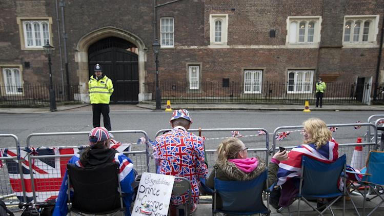 Royal fans wait outside St James's Palace, in the hope of catching a glimpse of members of the British royal family who will be attending the christening of Prince George in London, Wednesday, Oct. 23, 2013. Prince William and his wife Kate have asked seven people to be godparents to their son, Prince George, who will be christened at a major royal family gathering Wednesday, palace officials said. (AP Photo/Alastair Grant)