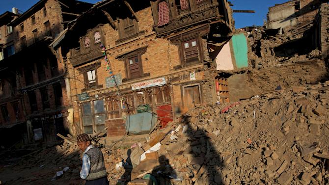 An earthquake victim walks along a street near collapsed houses in Sankhu, on the outskirts of Kathmandu