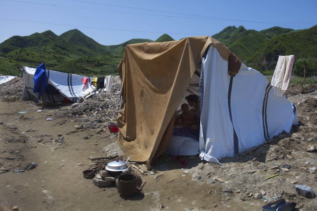 In this Monday, Aug 13, 2012 photo, a displaced North Korean women and her child, left homeless by July flooding, sit inside their temporary tent set up in their destroyed neighborhood in Ungok, North