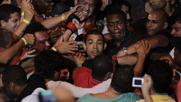 Jose Aldo of Brazil (C) celebrates with his fans after defeating Chad Mendes of the U.S. (not pictured) during the Ultimate Fighting Championship (UFC) Rio, a professional mixed martial arts (MMA) competition, in Rio de Janeiro