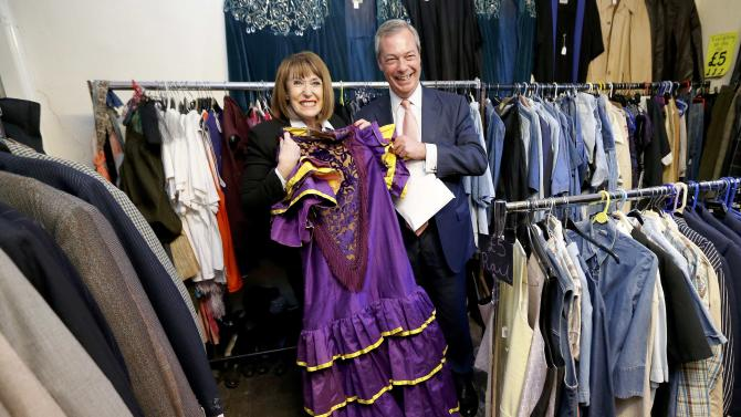 The leader of the United Kingdom Independence Party (UKIP) Nigel Farage poses with shop owner Debbie Barwick and a dress in the party's colours during a visit to a small business that has expressed its support for the party, in Canterbury southern England