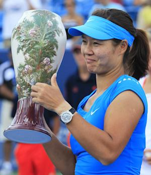 Li Na, from China, gives a thumbs-up while holding the championship trophy after defeating Angelique Kerber, from Germany, 1-6, 6-3, 6-1 during the women's final at the Western & Southern Open tennis tournament on Sunday, Aug. 19, 2012, in Mason, Ohio. (AP Photo/Al Behrman)