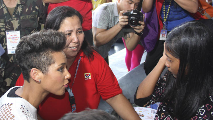 In this photo released by the Philippine Air Force, Grammy-winning singer Alicia Keys, left, talks to a typhoon survivor as she visits the Villamor Air Base in suburban Pasay, south of Manila, Philippines, Monday Nov. 25, 2013. Keys visited the air force base to bring cheer to hundreds of evacuees from eastern Philippine provinces wracked by Typhoon Haiyan earlier this month. (AP Photo/Philippine Air Force)