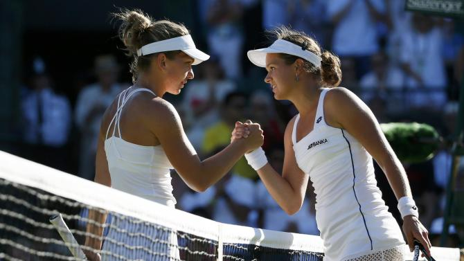 Jana Cepelova of Slovakia shakes hands with Simona Halep of Romania after winning their match at the Wimbledon Tennis Championships in London