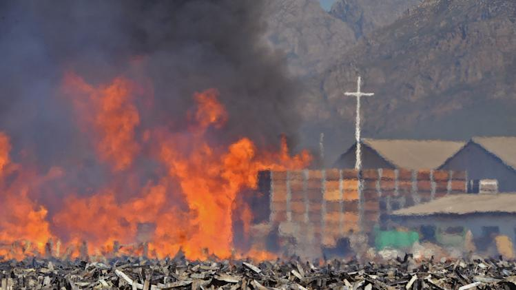 The remainder of 18,000 empty fruit containers after they were set alight by farm workers in Wolseley, South Africa, Wednesday, Nov. 14, 2012. Violent protests by farm workers have erupted in South Africa after weeks of unrest in the country's mining industry. Television images showed protesters overturn a police truck and set fires in the streets Wednesday in a town in South Africa's Western Cape. The workers have been protesting their wages, saying they want a minimum wage of $17 a day. Currently, workers make about half that amount a day. (AP Photo)