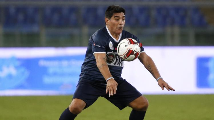 "Former soccer star Maradona controls the ball during a special interreligious ""Match for Peace"" at the Olympic stadium in Rome"