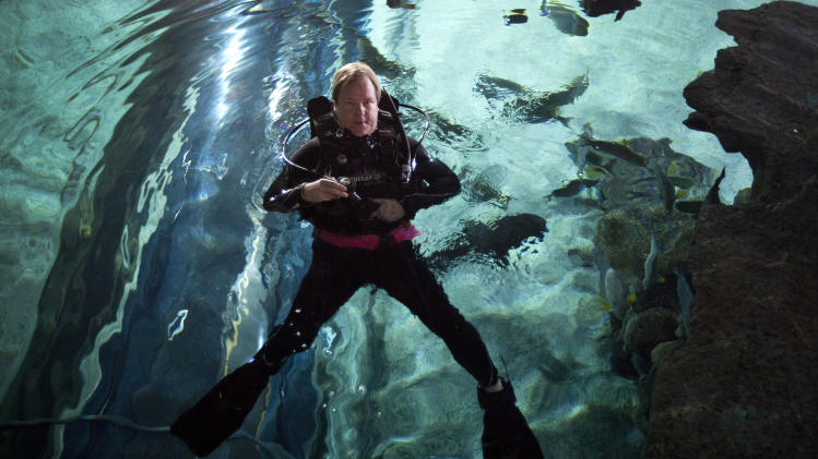 "In this photo taken on Saturday, July 28, 2012, American journalist and diving instructor Steven Schwankert in diving suit swims inside the Blue Zoo aquarium in Beijing, China. A lifelong scuba diving obsession led Schwankert to the tale of the HMS Poseidon and the startling discovery that the British submarine, which sank off the northeastern coast of China in the 1930s, had been raised by the Chinese in 1972. That revelation lies at the heart of Schwankert's upcoming book, ""The Real Poseidon Adventure: China's Secret Salvage of Britain's Lost Submarine"" and an accompanying documentary film chronicling his search for answers about what became of the sunken vessel. (AP Photo/Andy Wong)"