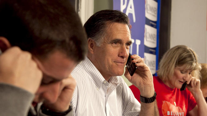 Republican presidential candidate, former Massachusetts Gov. Mitt Romney, center, flanked by campaign volunteers Jordan Furr, left, and Sherrie-Kaye Miller, both of Mechanicsburg, Pa., telephones a potential voter from a call center at his Pennsylvania campaign headquarters in Harrisburg, Pa., Thursday, April 5, 2012. (AP Photo/Steven Senne)