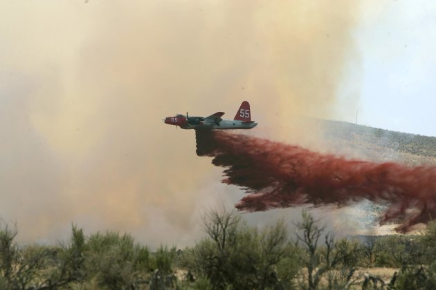 FILE - In this file photo made July 13, 2006, a P2-V Neptune air tanker drops retardant on a wildfire southwest of Elko, Nev. An air tanker dropping retardant on a remote wildfire along the Utah-Nevad