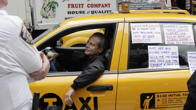 FILE - In this file photo of  Oct. 4, 2011, a New York City taxi driver, displaying signs objecting to legislation that would allow livery cabs to pick up street hails in the outer boroughs, drives by a rally outside of New York Gov. Andrew Cuomo's office, in New York. Despite the approval of the New York City budgets, questions still remain over the fate of $685 million at play as a judge mulls whether to allow livery cabs to make street hails in upper Manhattan and the city's other boroughs. (AP Photo/Richard Drew, File)