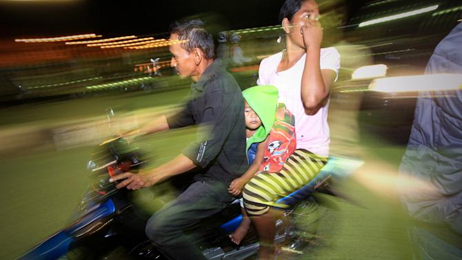 People on motorcycles flee after a strong earthquake hit in Aceh, Indonesia, Tuesday, Jan. 22, 2013.  A strong, shallow earthquake rocked parts of western Indonesia early Tuesday, killing a 9-year-old girl, panicking residents and ruining homes. Several other people were injured. (AP Photo/Heri Juanda)