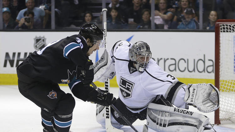 San Jose Sharks' Logan Couture, left, takes a shot against Los Angeles Kings goalie Jonathan Quick (32) during the second period of Game 1 of an NHL hockey first-round playoff series Thursday, April 17, 2014, in San Jose, Calif. (AP Photo/Ben Margot)