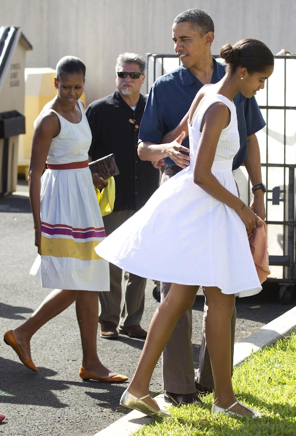 President Barack Obama, second from right, first lady Michelle Obama, left, and their daughters Malia, right, and Sasha, not seen, arrive to attend Christmas service at the Kaneohe bay Chapel on Marine Corps Base Hawaii, Sunday, Dec. 25, 2011, in Kaneohe, Hawaii. (AP Photo/Carolyn Kaster)