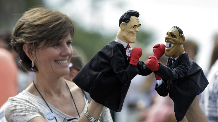 Lynn Armstrong Coffin and Eric Papalini, not shown, of PunchingPoliticians.com hold puppets of Republican presidential candidate and former Massachusetts governor Mitt Romney and President Obama boxing before a campaign rally at the Ringling Museum of Art Thursday, Sept. 20, 2012, in Sarasota, Fla. (AP Photo/Chris O'Meara)