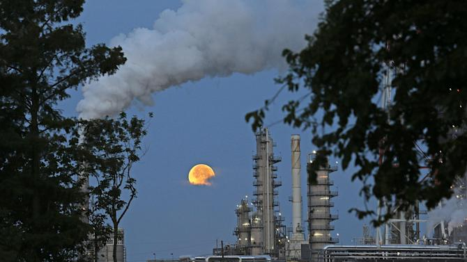 """The larger-than-normal full moon referred to as Supermoon is seen setting beyond a refinery in Norco, La., Sunday, June 23, 2013. The larger than normal moon called the """"Supermoon"""" happens only once this year as the moon on its elliptical orbit is at its closest point to earth and is 13.5 percent larger than usual. (AP Photo/Gerald Herbert)"""