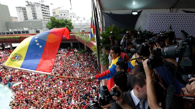 Venezuela's acting President Nicolas Maduro waves a Venezuelan flag over supporters after registering his candidacy for president to replace late President Hugo Chavez at the national electoral council in Caracas, Venezuela, Monday, March 11, 2013. Presidential elections were announced to take place on April 14, after Maduro announced on March 5 that Chavez had died. (AP Photo/Ariana Cubillos)