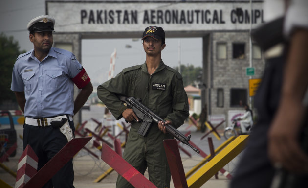 Pakistani security stand guard at the entrance of Pakistan&#39;s air force base in Kamra about 85 kilometers (50 miles) northwest of Islamabad, Pakistan, Thursday, Aug. 16, 2012. Militants attacked an air force base in northwest Pakistan filled with F-16s and other aircraft before dawn Thursday, sparking a heavy battle with security forces that left parts of the base in flames, officials said. (AP Photo/B.K. Bangash)