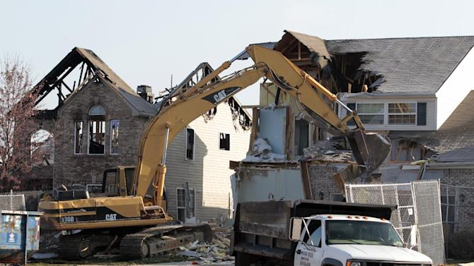 The first of several homes is demolished in Indianapolis, Tuesday, Nov. 27, 2012.  City building inspectors last week ordered the demolition of 29 houses by Dec. 20. Four other homes, including two that were leveled in the Nov. 10 explosion, are being maintained as police investigate what they believe was an intentional natural gas explosion. (AP Photo/Michael Conroy)