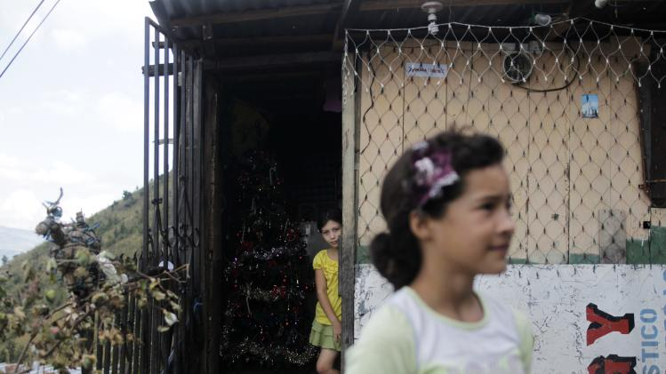 Girls stand at their home in the low-income neighborhood of El Picachito in Tegucigalpa