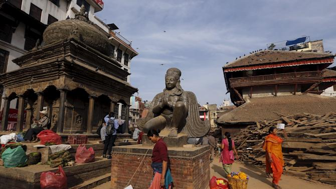 Nepalese people walk past destroyed temples at Bashantapur Durbar Square, after the earthquake in Kathmandu