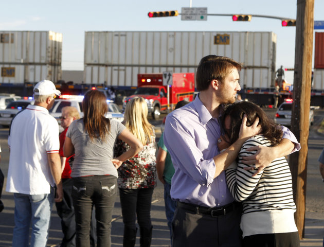 Bystanders react as emergency personnel work the scene where a trailer carrying wounded veterans in a parade was struck by a train in Midland, Texas, Thursday, Nov. 15, 2012. &quot;Show of Support&quot; preside