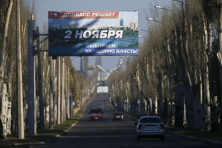 Cars drive past an election information board in Yasynuvata