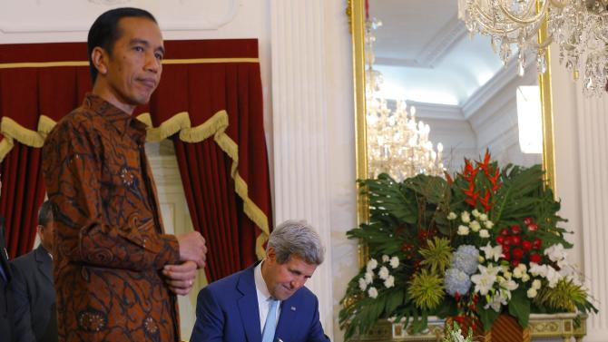 U.S. Secretary of State John Kerry signs a guest book as he pays a visit to Indonesia's newly inaugurated President Joko Widodo to the Presidential Palace in Jakarta