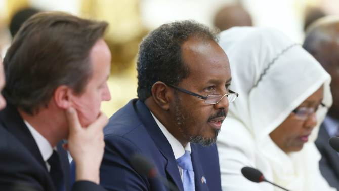 Britain's Prime Minister David Cameron, left, listens as Somali President Hassan Sheikh Mohamud speaks at the Somalia conference in London, Tuesday May 7, 2013. British Prime Minister David Cameron is welcoming Somalia's president and a host of international leaders to London for a conference aimed at securing support for the government in Mogadishu after two decades of conflict. (AP Photo/Andrew Winning, Pool)