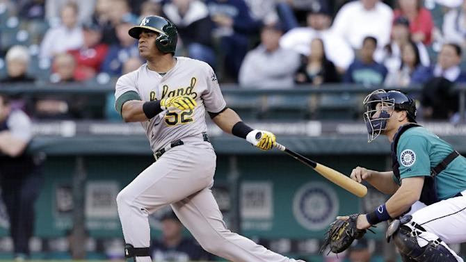Oakland Athletics' Yoenis Cespedes, left, watches the path of his home run as Seattle Mariners catcher Mike Zunino looks on in the first inning of a baseball game on Friday, June 21, 2013, in Seattle. (AP Photo/Elaine Thompson)