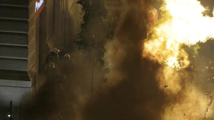 A petrol bomb thrown by protesters explodes near riot police in front of parliament during clashes in Athens, Wednesday Nov. 7, 2012. Greece's fragile coalition government faces its toughest test so far when lawmakers vote later Wednesday on new painful austerity measures demanded to keep the country afloat, on the second day of a nationwide general strike. The euro13.5 billion ($17.3 billion) package is expected to scrape through Parliament, following a hasty one-day debate. But potential defections could severely weaken the conservative-led coalition formed in June with the intention of keeping Greece in the euro. (AP Photo/Dimitri Messinis)