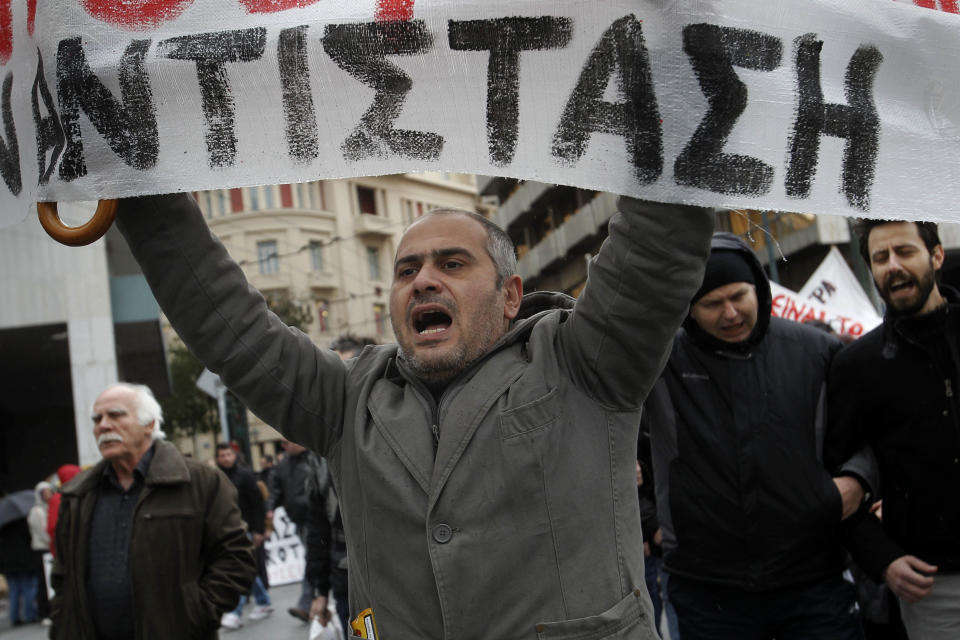 A protester holds a banner which reads in Greek: ''resistance''  during a 24-hour strike on Tuesday, Feb. 7, 2012. A general strike against the impending cutbacks  stopped train and ferry services nationwide, while many schools and banks were closed and state hospitals worked on skeleton staff. (AP Photo/Petros Giannakouris)