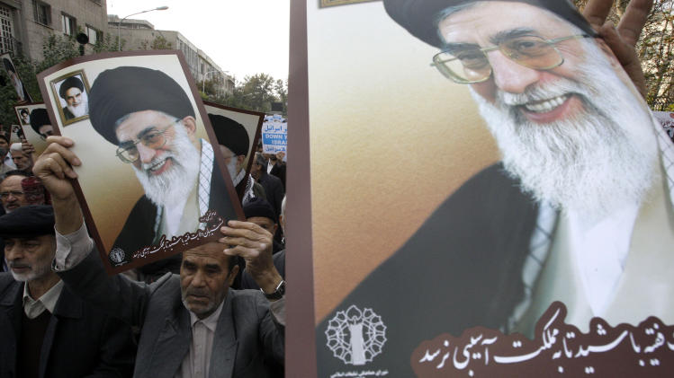 In this picture taken on Friday, Nov. 16, 2012, Iranian worshippers hold posters showing supreme leader Ayatollah Ali Khamenei, and late revolutionary founder Ayatollah Khomeini, in a pro-Palestinian demonstration after Friday prayer, in Tehran, Iran. (AP Photo/Vahid Salemi)