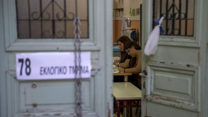 Voting officials are seen inside a polling station during a referendum in Athens, Greece