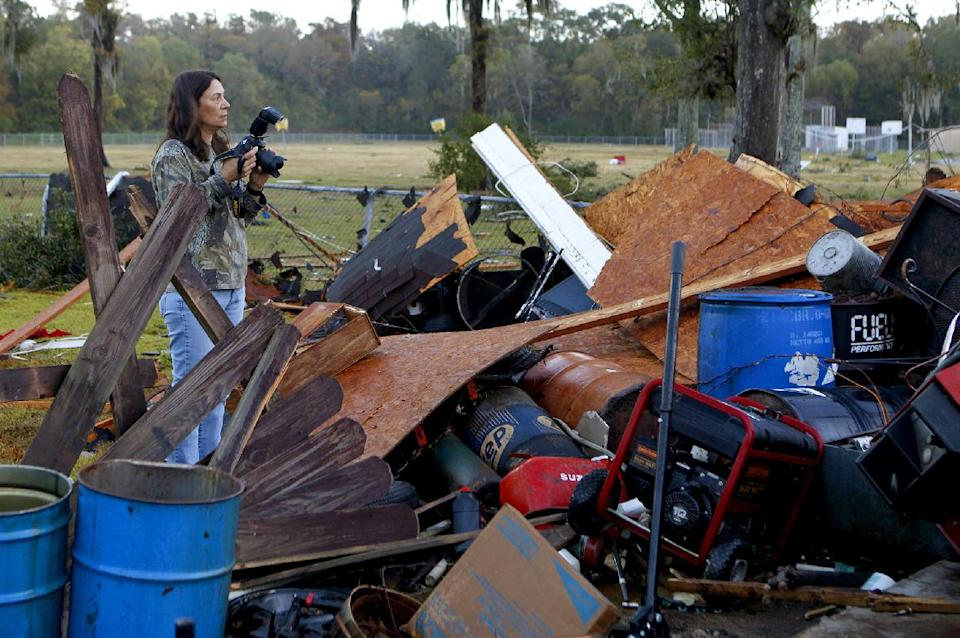 Kim Eskind takes photos of her parents' house after strong winds from a suspected tornado damaged their home Wednesday, November 16, 2011 in Houma, La.   No one was injured. (AP Photo/The Houma Courier, Julia Rendleman)