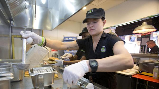 In this Tuesday, Jan. 27, 2015, photo, BurgerFi restaurant employee Elia Carranza prepares to fry eggs for an order at the Aventura, Fla., restaurant. The company plans to nearly double in size from their existing 65 restaurants this year. (AP Photo/Wilfredo Lee)