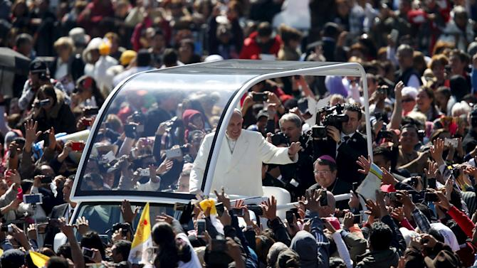 Pope Francis waves to the crowd from the popemobile in Zocalo Square in Mexico City