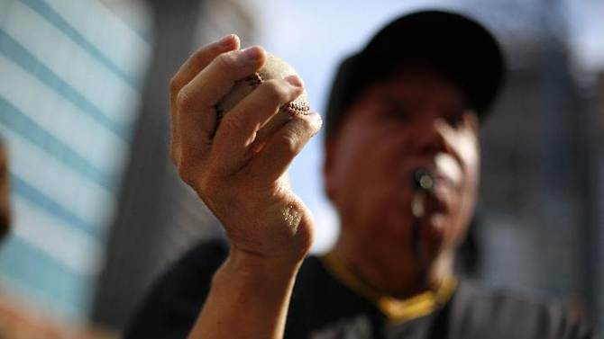 A Pittsburgh Pirates fan holds a baseball during a Pirates pep rally in downtown Pittsburgh Tuesday, Sept. 30, 2014. The Pirates face the San Francisco Giants in the wild card game in Pittsburgh Wednesday night. (AP Photo/Gene J. Puskar)