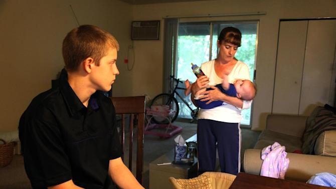 In this Sept. 16, 2011 photo, Kris Fallon holds her 4-month-old daughter Addison, in Palatine, Ill., as her 15-year-old son Gared Fallon looks on. The Fallon family has been living in poverty for nearly two years. (AP Photo/Robert Ray)