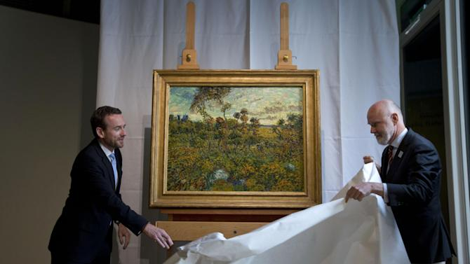 "CAPTION CORRECTION, CORRECTS SPELLING OF SURNAME TO REFLECT AP STYLE - Van Gogh Museum director Axel Rueger, left, and senior researcher Louis van Tilborgh, right, unveil ""Sunset at Montmajour"" during a press conference at the Van Gogh Museum in Amsterdam, Netherlands, Monday Sept. 9, 2013. The museum has identified the long-lost painting which was painted by the Dutch mater in 1888, the discovery is the first full size canvas that has been found since 1928 and will be on display from Sept. 24. (AP Photo/Peter Dejong)"