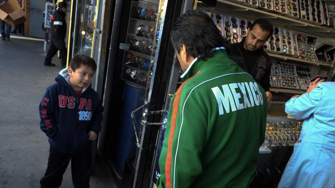 Mexican immigrant Roberto Garcia, center, and son Alan, left, look at wrist watches while shopping in Los Angeles, Monday, Jan. 28, 2013. Seeking swift action on immigration, President Barack Obama on Tuesday will try to rally public support behind his proposals for giving millions of illegal immigrants a pathway to citizenship, as well as making improvements to the legal immigration system and border security. (AP Photo/Jae C. Hong)