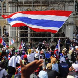 Anti-government protesters wave flags after they entered the compound of Government House, the site of fierce clashes with police over the last few days in Bangkok