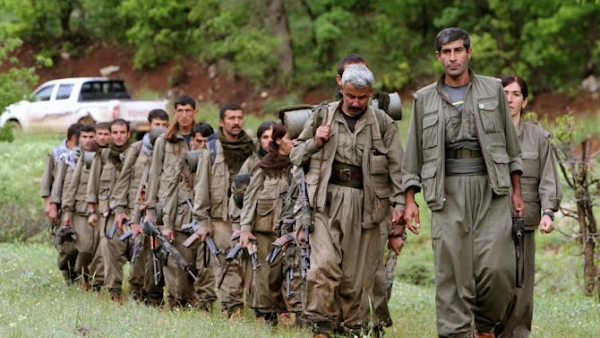 A group of armed Kurdish fighters from the Kurdistan Workers Party (PKK) enter northern Iraq in the Heror area, northeast of Dahuk, 260 miles (430 kilometers) northwest of Baghdad, Tuesday, May 14, 2013. The first of Kurdish fighters from Turkey have entered northern Iraq as part of a peace deal to end a long uprising, despite Iraqi objections to the transfer. Comrades greeted 13 armed men and women from the Kurdistan Workers Party (PKK) at a ceremony in Heror in Iraq's self-ruled Kurdish area. The central government in Baghdad has rejected the deal, warning that the entry of more armed Kurdish fighters could harm the country's security. (AP Photo/ Ceerwan Aziz)