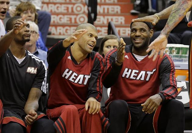 Miami Heat forward LeBron James, right, forward Shane Battier, center, and center Chris Bosh, left, congratulate Chris Andersen as he comes off the court during the fourth quarter of an NBA basketball