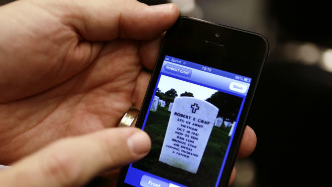 Army Col. John Schrader demonstrates the ANC Explorer application for Arlington National Cemetery, on his phone, after a news conference in Washington, Monday, Oct. 22, 2012. Arlington National Cemetery plans to make available to the public the detailed geospatial database it has developed over several years while overhauling its records and responding to reports of misidentified remains. The database will be available over the Internet and through a mobile phone app that visitors to the cemetery can take with them to find a specific gave anywhere in the cemetery. (AP Photo/Jacquelyn Martin)