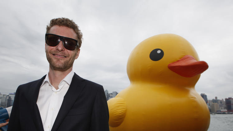 Dutch artist Florentijn Hofman poses with his creation, a giant Rubber Duck in Hong Kong Thursday, May 2, 2013. Since 2007 the 16.5-meter (54-feet)-tall Rubber Duck has traveled to various cites including Osaka, Sydney, Sao Paulo and Amsterdam.  (AP Photo/Kin Cheung)