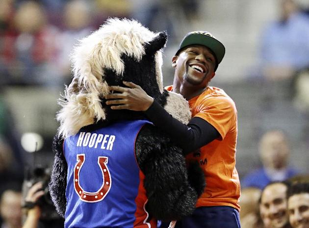 Boxer Floyd Mayweather Jr., right, clowns around with Hooper, the Detroit Pistons mascot during the second half of an NBA basketball game between the Pistons and the Chicago Bulls in Auburn Hills, Mic