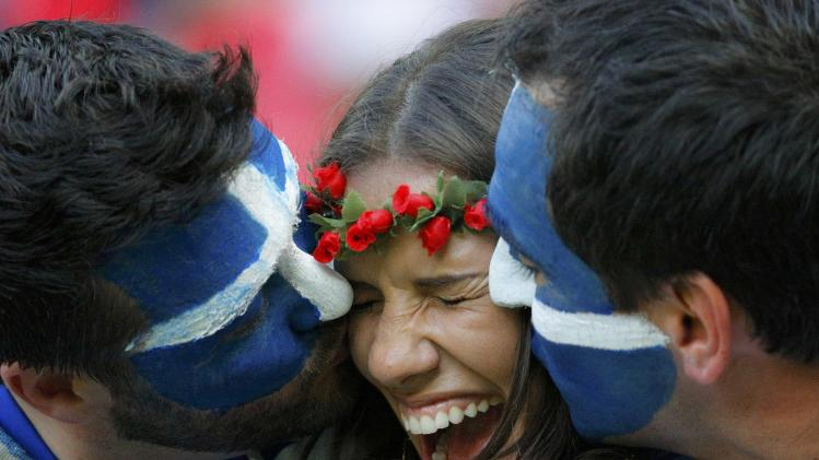 Fans of Greece kiss before their 2014 World Cup round of 16 game against Costa Rica at the Pernambuco arena in Recife
