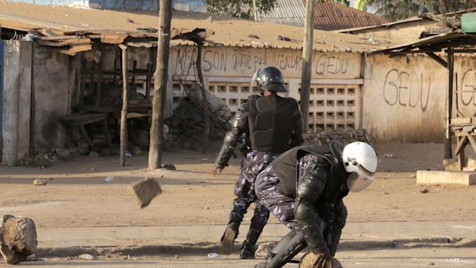In this photo taken on Friday, Nov. 21, 2014, Togo troops clear rocks from the road during clashes with protesters calling for the president to withdraw from a presidential vote in March 2015, in Lome, Togo. Security forces in Togo used rubber bullets and tear gas to disperse thousands of demonstrators calling for term limits that would bar President Faure Gnassingbe from running for a third term in office. (AP Photo/Erick Kaglan)