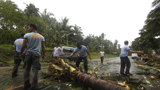 Philippine National Police clear a highway of toppled coconut trees after Typhoon Bopha made a landfall in Compostela Valley in southeastern Philippines Tuesday Dec. 4, 2012. A Philippine governor says at least 33 villagers and soldiers have drowned when torrents of water dumped by the powerful typhoon rushed down a mountain, engulfing the victims and bringing the death toll from the storm to about 40. (AP Photo/Karlos Manlupig)
