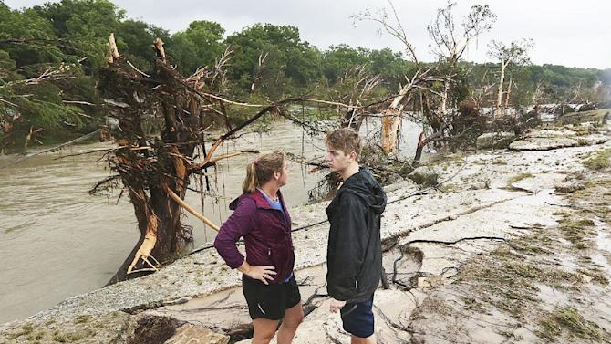 Shelly Guzal and her son, Grant, 17, stand by the Blanco River by where an A-frame house owned by the Carey family once stood in Wimberley, Texas, Monday, May 25, 2015. Corpus Christi resident Jonathan McComb, 36, and his family were guest in the house when it was swept away by floodwaters Saturday night. McComb was able to escape but his wife, Laura, 33, and their children, Leighton, 4 and Andrew, 6, are missing. (Jerry Lara/The San Antonio Express-News via AP)